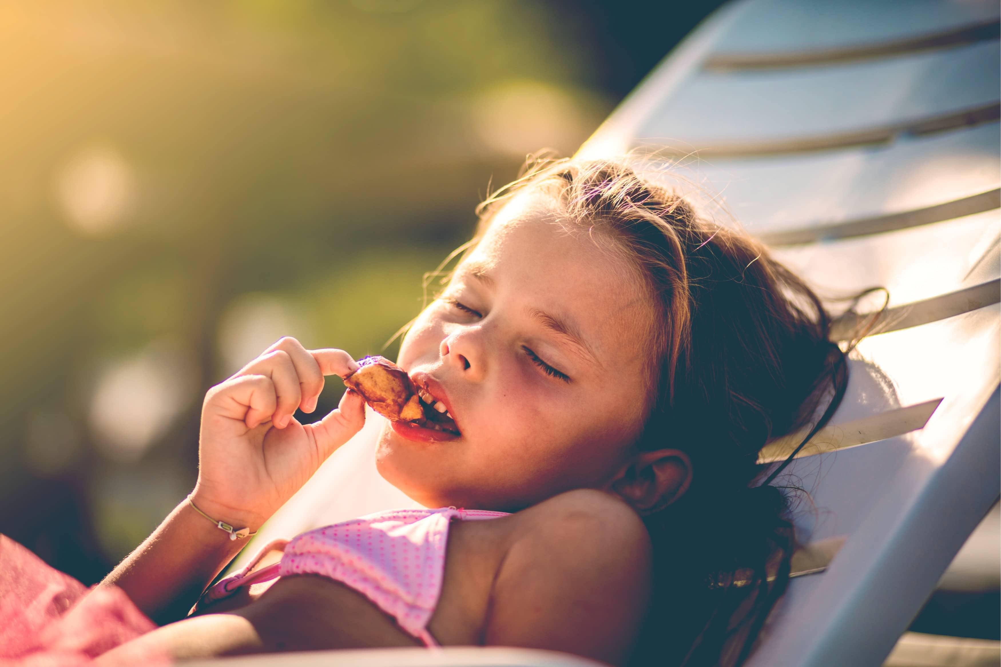 little girl eat at beach