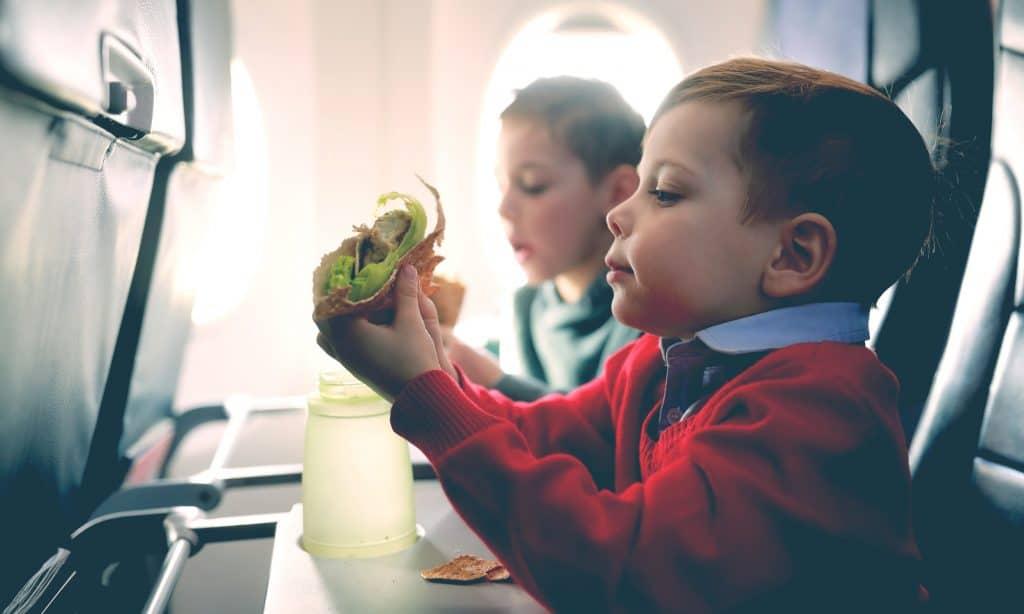 little kid eat in a plane