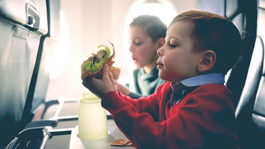 little kid eat in a plane